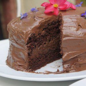 Cobertura: Derreta o chocolate em banho-maria. Bata a manteiga na batedeira até que esteja bem cremosa. Em seguida, adicione o açúcar de confeiteiro peneirado, e bata novamente até que forme um creme fofo. Então adicione delicadamente o chocolate e a baunilha e misture bem até que forme um creme brilhante e liso. Espalhe 1/4 do creme de chocolate sobre um dos bolos. Acomode o outro bolo em cima e cubra todo o topo e laterais com o restante do creme de chocolate.
